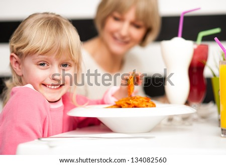 Cute girl kid enjoying meal and juice in restaurant with her mother.