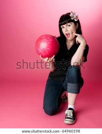Cute girl kneeling on one knee holding a bowling ball