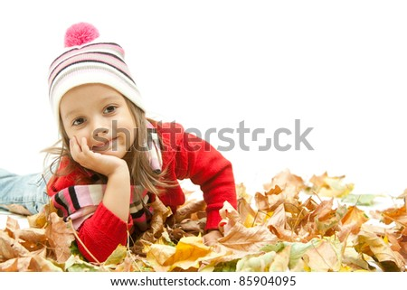 cute girl laying in colored autumn leaves