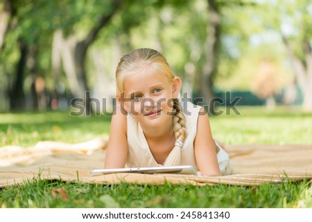 Cute girl lying in park and using tablet pc #245841340