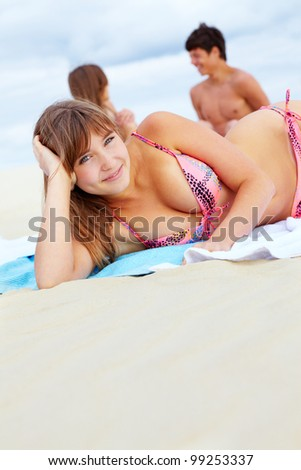 Cute girl lying on beach and looking at camera, her friends in the background enjoying themselves