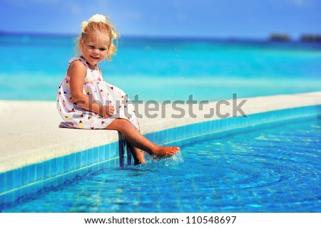 cute girl near pool looking at turquoise ocean
