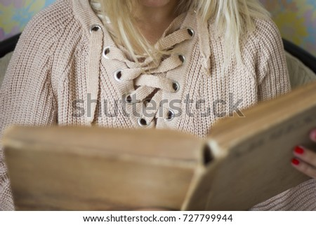 Cute girl on a comfortable chair, reading a book, the concept of comfort and hipster #727799944