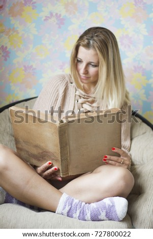 Cute girl on a comfortable chair, reading a book, the concept of comfort and hipster #727800022