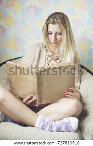 Cute girl on a comfortable chair, reading a book, the concept of comfort and hipster #727810918