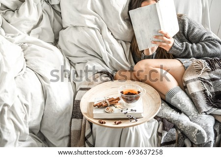 Cute girl on a comfortable chair with tea ,reading a book, the concept of comfort and hipster #693637258
