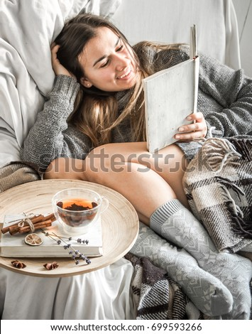 Cute girl on a comfortable chair with tea ,reading a book, the concept of comfort and hipster #699593266