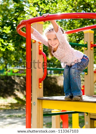 Cute girl on outdoor playground equipment