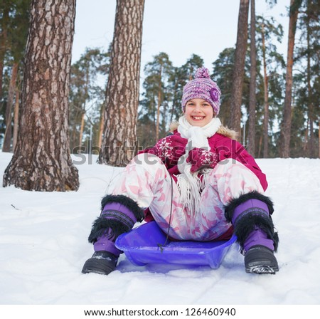 Cute girl on sleds in snow forest.