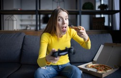 Cute girl plays the game on the console and eats pizza