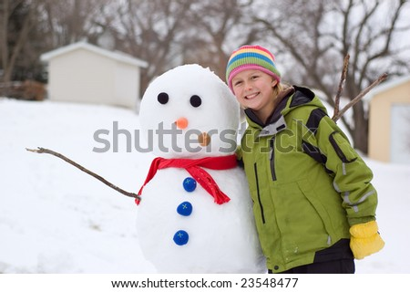 Cute Girl Poses Next to the Snowman She Made
