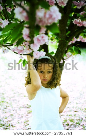 Cute girl posing under a japanese cherry-blossom tree. Cross-processed