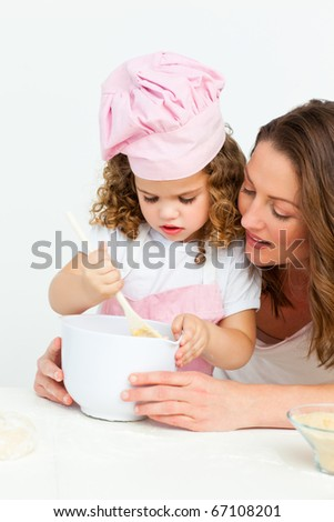 Cute girl  preparing a cake with her mother in the kitchen