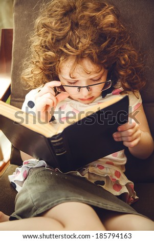Cute girl reading a book. Photo toning in brown.