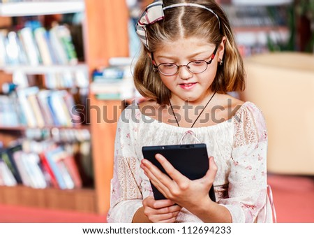 Cute girl reading an electronic book in a library