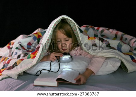 cute girl reading in bed with a book light