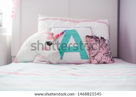 Cute girl's bedroom with monogrammed throw pillow, unicorn pillow, and sequin pillow
