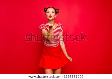 Cute girl send a kiss for you! Adorable young girl with nice make up wearing striped tshirt and red skirt isolated on bright background and sends air kiss from open palm