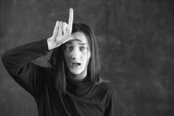Cute girl shows loser sign. Failure and fiasco concept. Black and white photo with copy space.