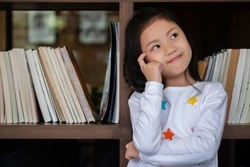 cute girl sitdown smiled and look up in the room, children concept, education concept