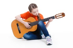 Cute girl sitting and plays on the acoustic guitar -  isolated on white background.