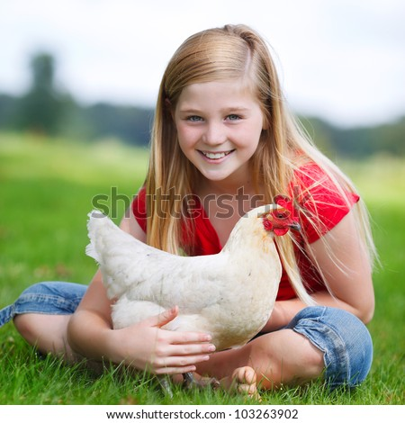 cute girl sitting in the grass with her white chicken