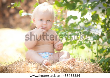 cute girl sitting on a large hay bale under the tree