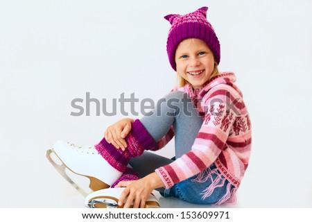 cute girl sitting on ice skates - stock photo