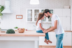 cute girl sitting on the table and father standing on the kitchen and looking at each other, side view