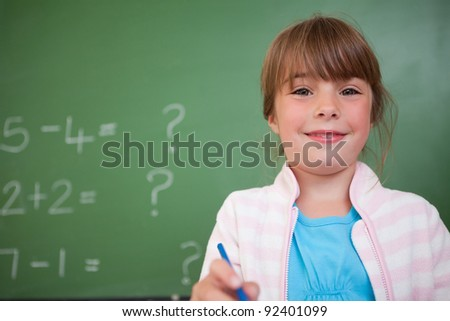 Cute girl standing up in front of a blackboard