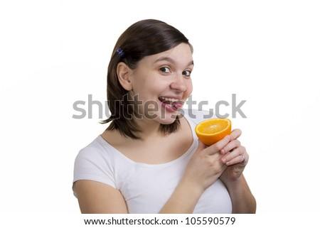 Cute girl starts to lick fresh orange