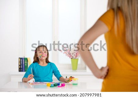 cute girl surprised by mother talking. little schoolgirl painting colorful drawing
