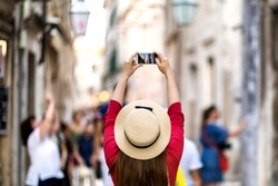 Cute girl takes pictures on a smartphone sights in a journey on the streets of Dubrovnik, Croatia. Solo travel. Share your impressions!