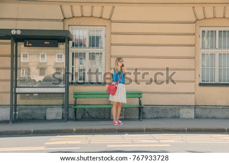 Cute girl talking on the phone and waiting for a bus in the city. #767933728