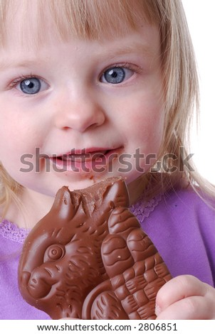Cute Girl Toddler Eating the Ear of a Chocolate Easter Bunny