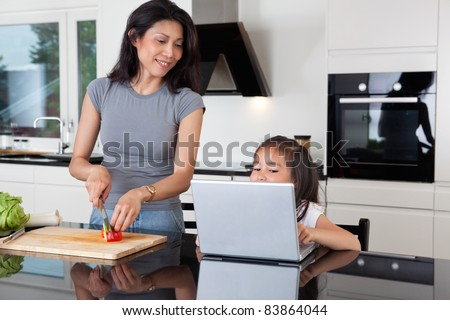 Cute girl using laptop while mother cuts vegetable in kitchen