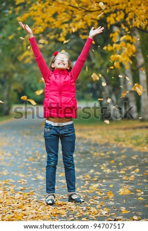 Cute girl walking in the autumn park. Rain, yellow leaves, tree.