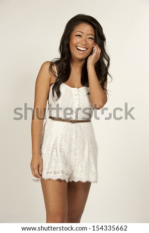Cute girl wearing a white lace romper laughing into her iPhone.