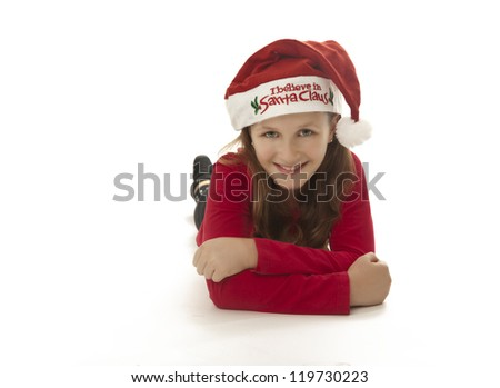 "cute girl wearing ""i believe in santa"" hat smiles to camera, lying down, copyspace,"