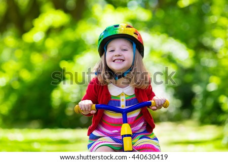 Cute girl wearing safety helmet riding her tricycle in sunny summer park. Kids ride bicycle. First bike for little child. Active toddler kid playing and cycling outdoors. Kids play in the garden.