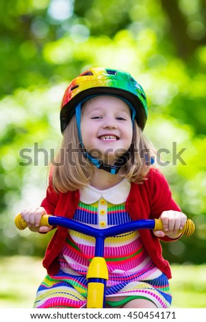ac24dd98dc1 Cute girl wearing safety helmet riding her tricycle in sunny summer park.  Kids ride bicycle