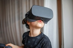 Cute girl wearing virtual reality googles at home, remote education experiment, future today, new online education, indoor lifestyle