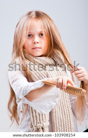 Cute girl wearing warm knitted scarf combing fine long blond hair