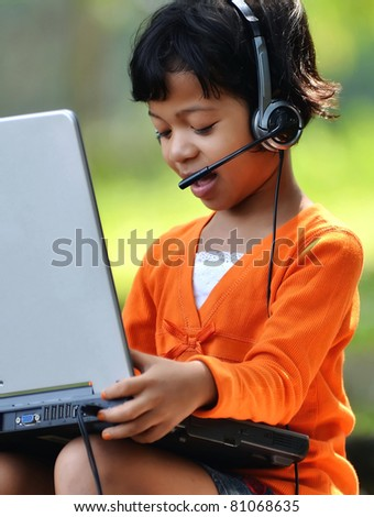Cute girl with a headset playing with laptop computer