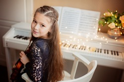 Cute girl with a violin in her hands sits near the piano, bokeh from a garland. Music concept