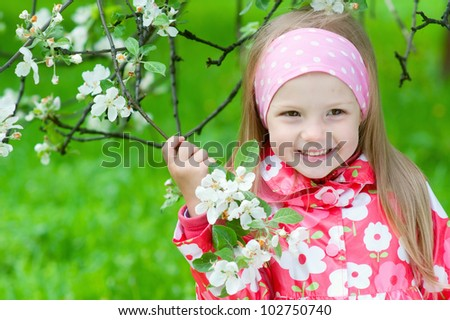 Cute girl with blossoming apple tree