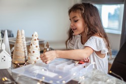 Cute girl with curly hair is handcrafting and decorating paper cone Christmas Tree with buttons, yarn and fairy lights. Concept of using crafted Christmas Tree and stop clearcutting. Hobby and leisure
