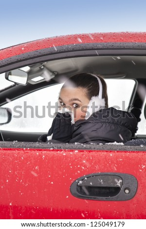 Cute girl with flu symptoms sneezes in a car on snowy  winter day. Using handkerchief closes mouth with her hands.
