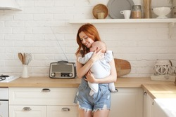Cute girl with ginger hair embracing adorable baby in blue bodysuit, cradling him sleep to music on radio, standing at kitchen counter and smiling. Pretty sister babysitting her infant niece