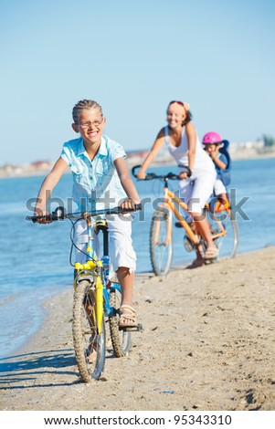 Cute girl with her mother and brother ride bikes along the beach. Focus on girl. Vertical view